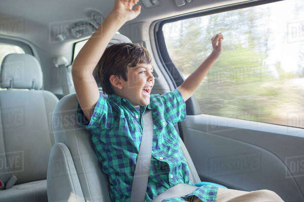 Enthusiastic boy cheering in back seat of car Royalty-free stock photo