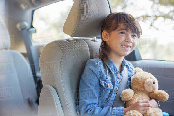 Happy girl with teddy bear in back seat of car Royalty-free stock photo