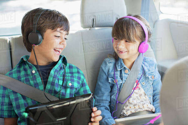 Happy brother and sister with headphones using digital tablets in back seat of car Royalty-free stock photo