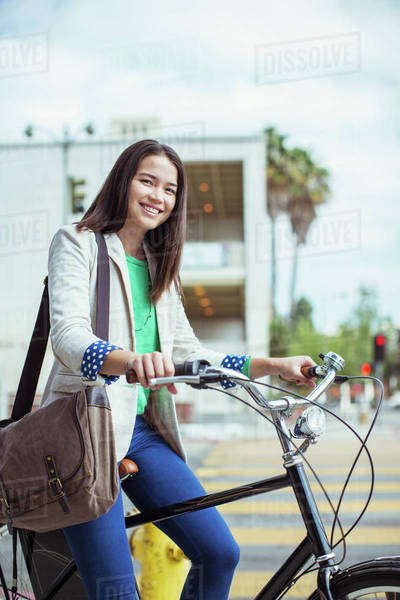 Portrait of smiling casual businesswoman on bicycle on urban street Royalty-free stock photo