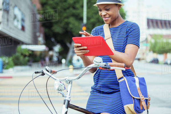 Casual businesswoman using digital tablet on bicycle on urban street Royalty-free stock photo