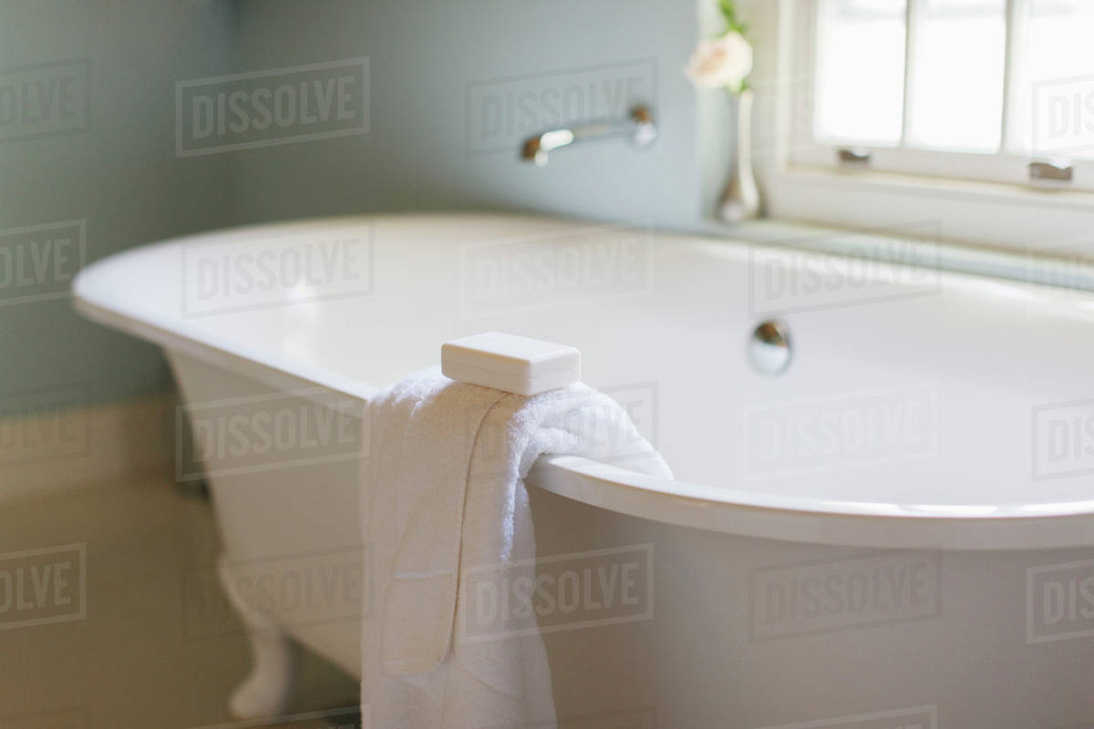 Bar soap and towel on ledge of claw foot tub - Stock Photo - Dissolve