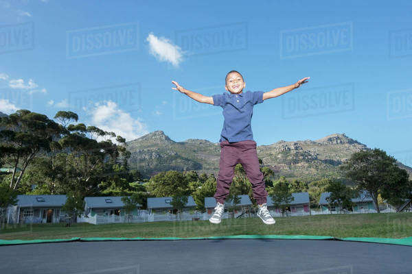 Boy jumping on trampoline outdoors Royalty-free stock photo