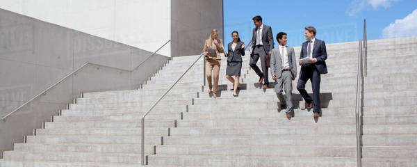 Business people talking and descending urban stairs Royalty-free stock photo