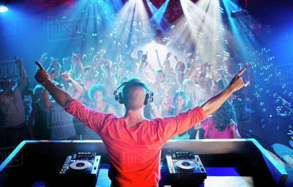 DJ with arms outstretched overlooking dance floor Royalty-free stock photo