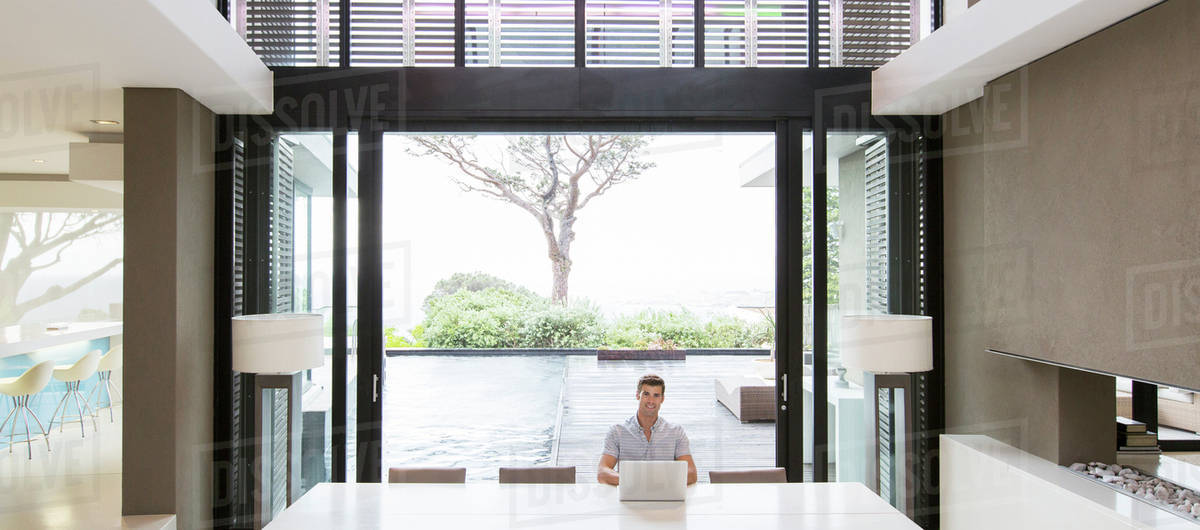 Young Man Using Laptop In Modern Dining Room With Patio Doors And Swimming Pool Background