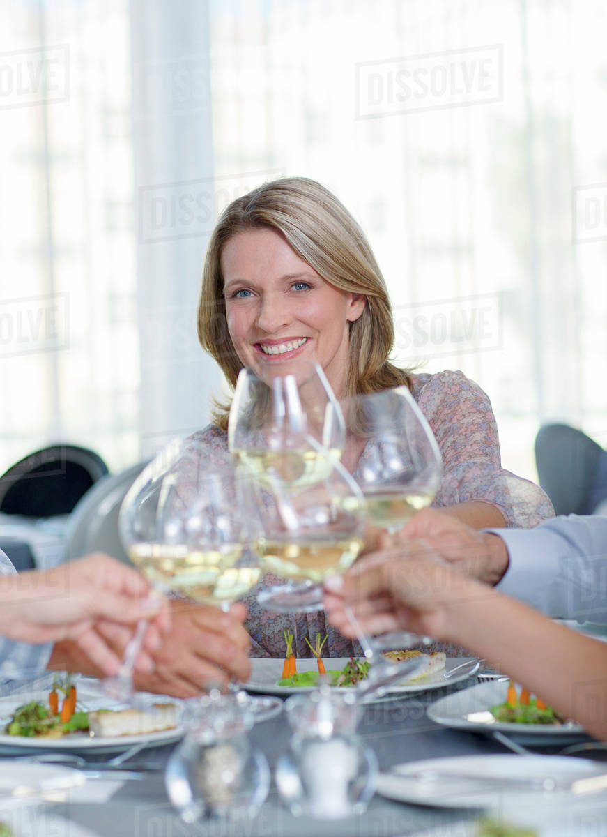 Portrait of smiling mature woman toasting with white wine in restaurant