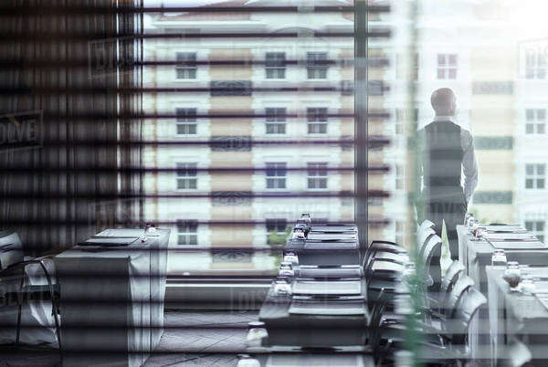 Young businessman standing in conference room looking out of window Royalty-free stock photo