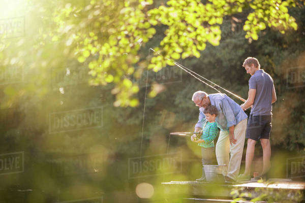 Boy, father and grandfather fishing in lake Royalty-free stock photo