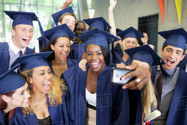 Group of smiling students in graduation gowns taking selfie on graduation day Royalty-free stock photo