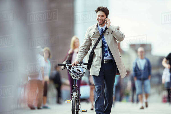 Businessman talking on cell phone pushing bicycle in city Royalty-free stock photo