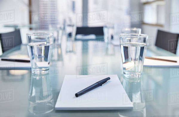 Part of modern conference room with table chairs, notepads, pens and glasses with water Royalty-free stock photo