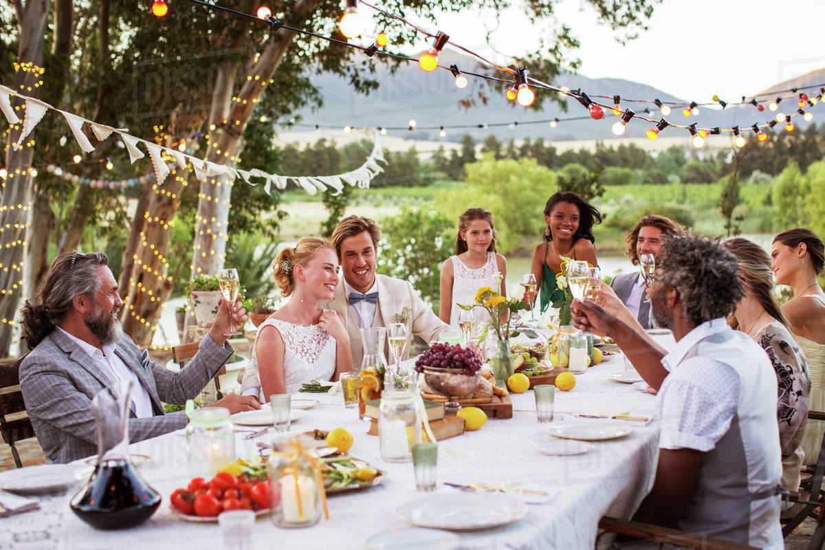 Young couple and their guests sitting at table during wedding reception in garden Royalty-free stock photo