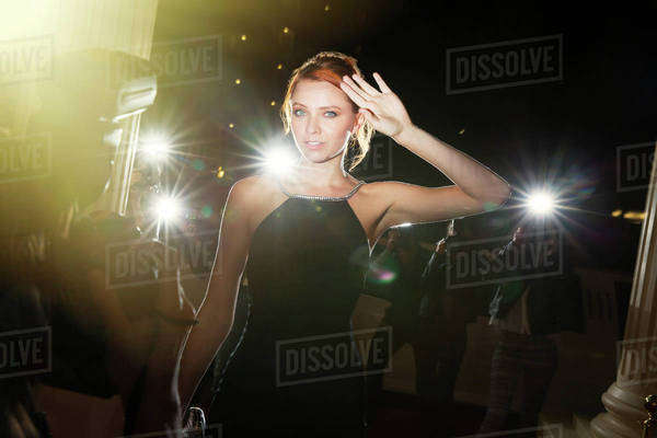 Portrait of confident celebrity being photographed by paparazzi at event Royalty-free stock photo