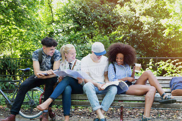 College students hanging out studying on park bench Royalty-free stock photo