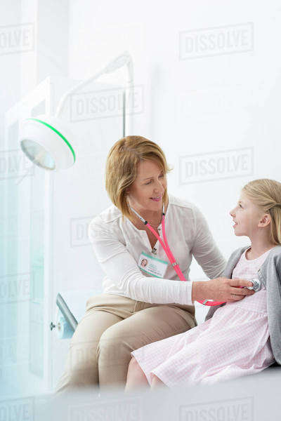 Pediatrician using stethoscope on girl patient in examination room Royalty-free stock photo