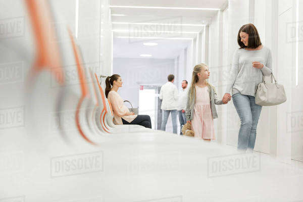 Mother and daughter holding hands walking in hospital corridor Royalty-free stock photo