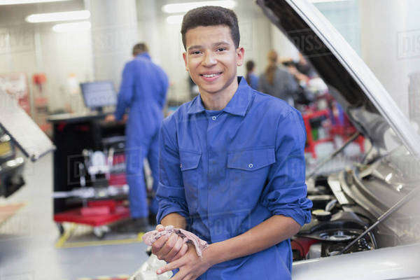 Portrait smiling mechanic leaning on car in auto repair shop Royalty-free stock photo