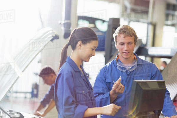 Mechanics discussing part at computer in auto repair shop Royalty-free stock photo