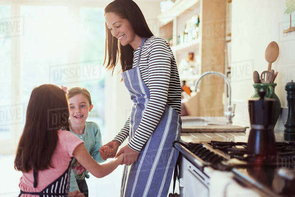 Mother and daughters holding hands in kitchen Royalty-free stock photo