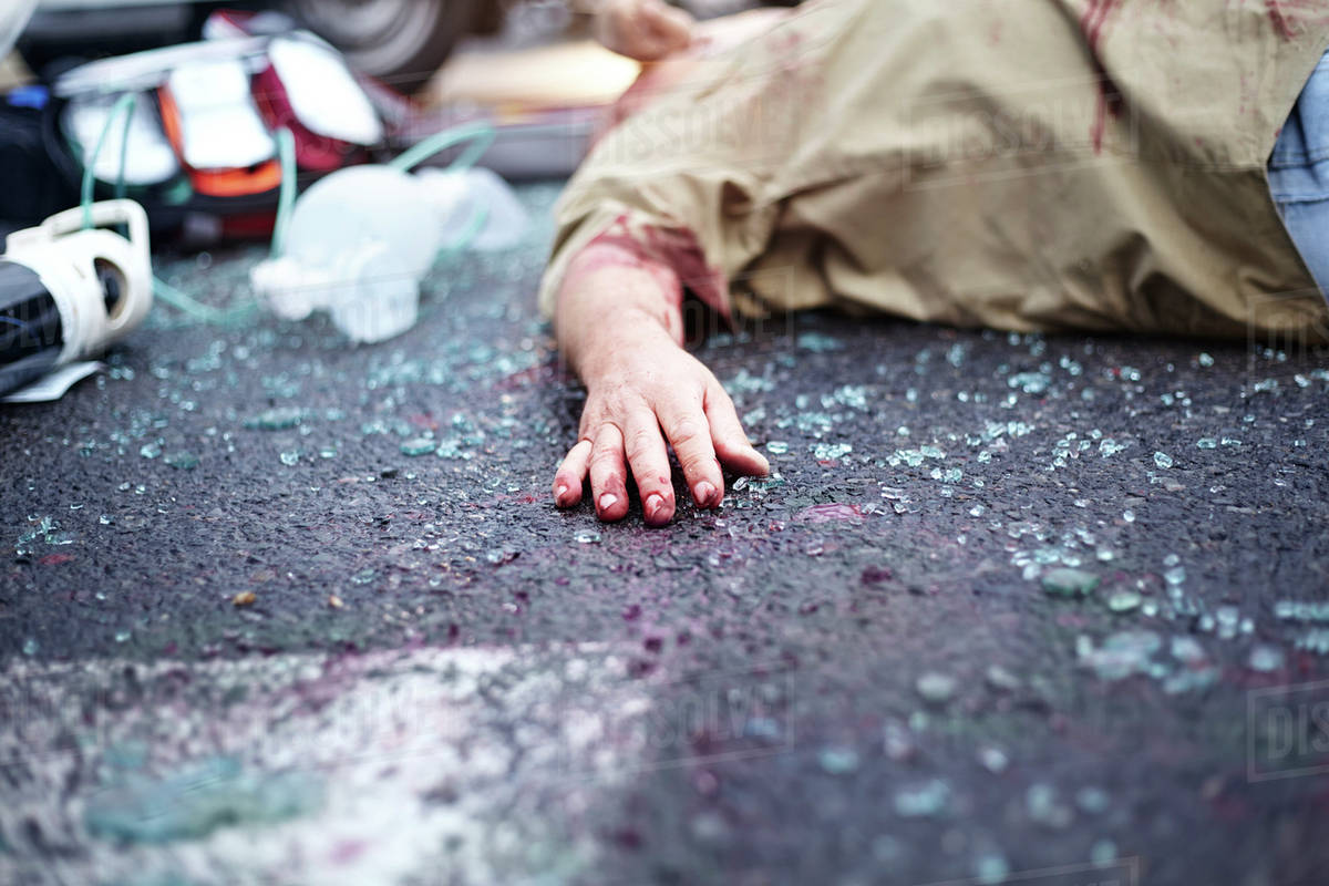 Bloody Hand Of Car Accident Victim In Road Among Shattered Glass