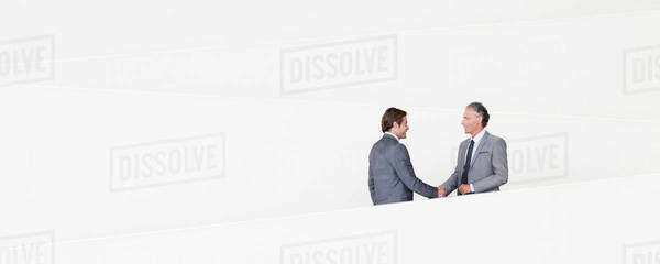 Businessmen shaking hands on modern staircase Royalty-free stock photo