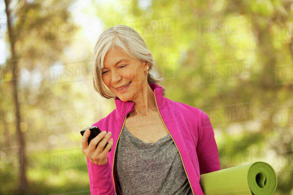 Older woman using cell phone outdoors Royalty-free stock photo