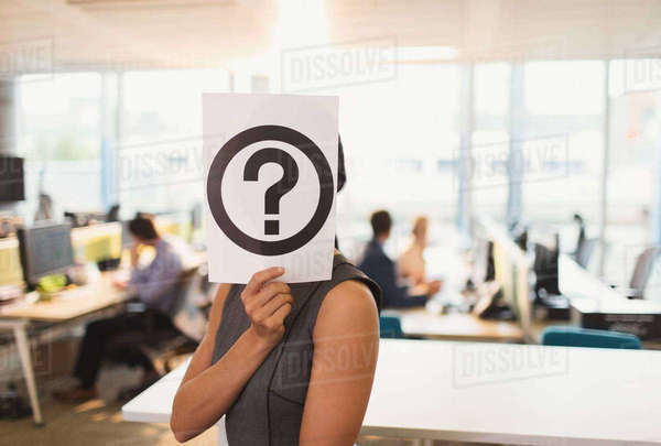 Portrait of businesswoman holding question mark printout over her face in office Royalty-free stock photo