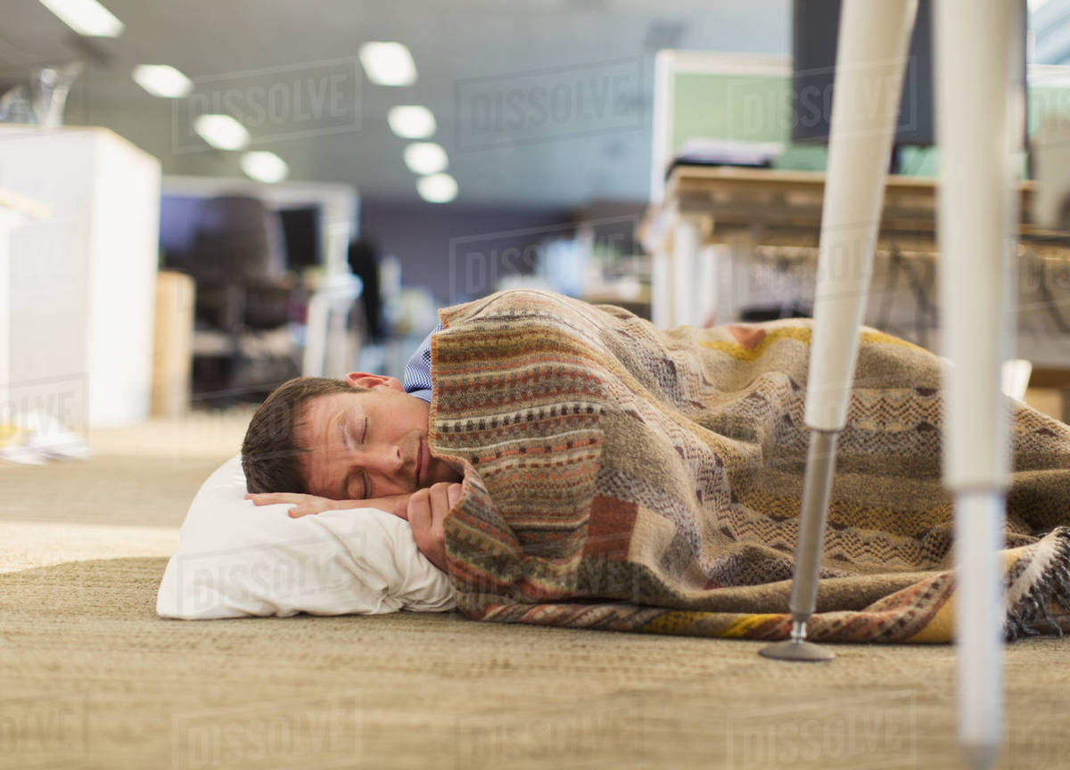 Businessman with pillow and blanket sleeping on office floor - Stock ...