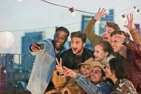 Enthusiastic young adult friends cheering and taking selfie at rooftop party Royalty-free stock photo