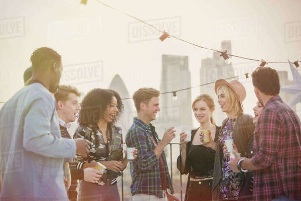Young adult friends drinking and enjoying rooftop party Royalty-free stock photo