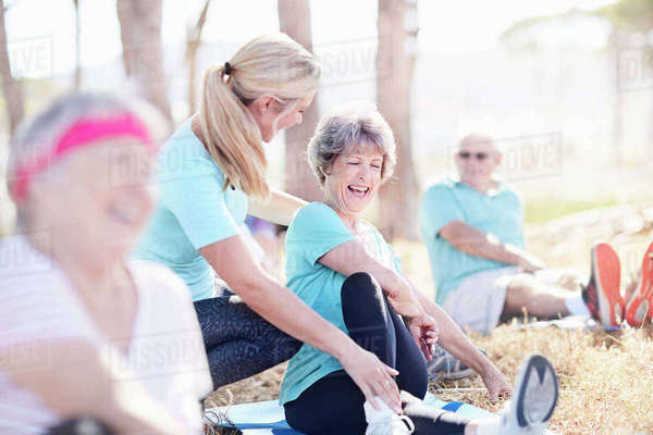 Yoga instructor guiding senior woman in sunny park Royalty-free stock photo