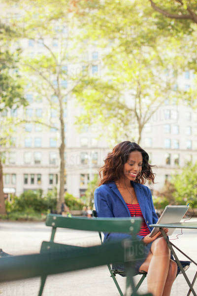 Woman using digital tablet at sidewalk cafe Royalty-free stock photo