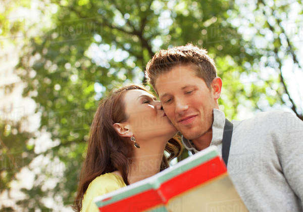 Woman kissing boyfriend in park Royalty-free stock photo