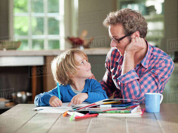 Father and son doing homework at kitchen table Royalty-free stock photo