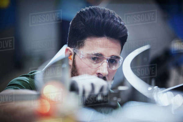 Worker examining pieces in steel factory Royalty-free stock photo