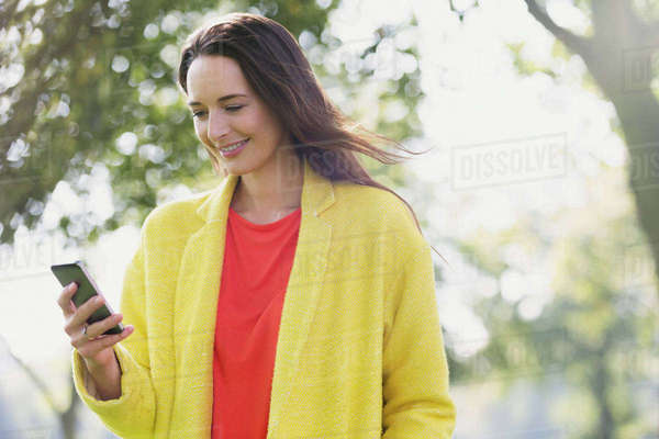 Smiling woman using cell phone in park Royalty-free stock photo