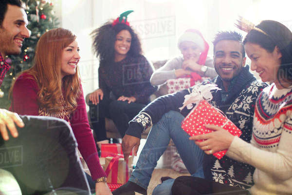 Friends opening Christmas gifts in living room Royalty-free stock photo