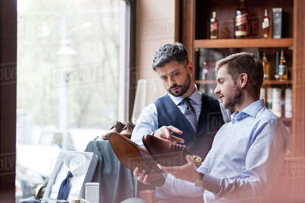 Businessmen examining dress shoes in menswear shop Royalty-free stock photo