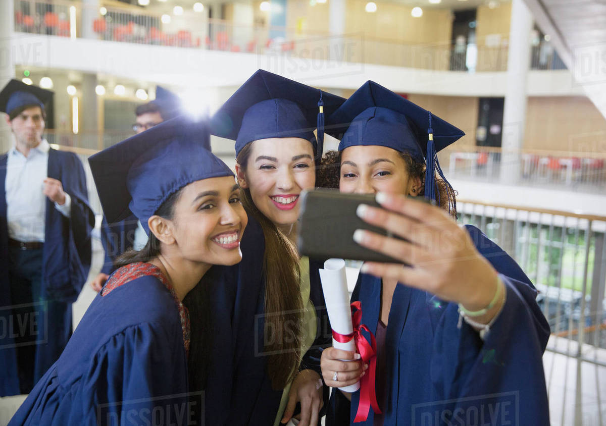 Female college graduates in cap and gown taking selfie - Stock Photo ...