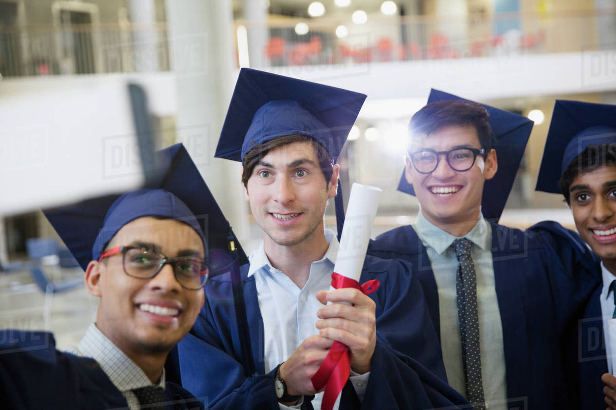 Male college graduates in cap and gown with diploma taking selfie ...