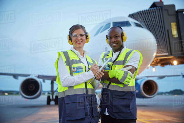 Portrait confident air traffic control ground crew workers near airplane on airport tarmac Royalty-free stock photo