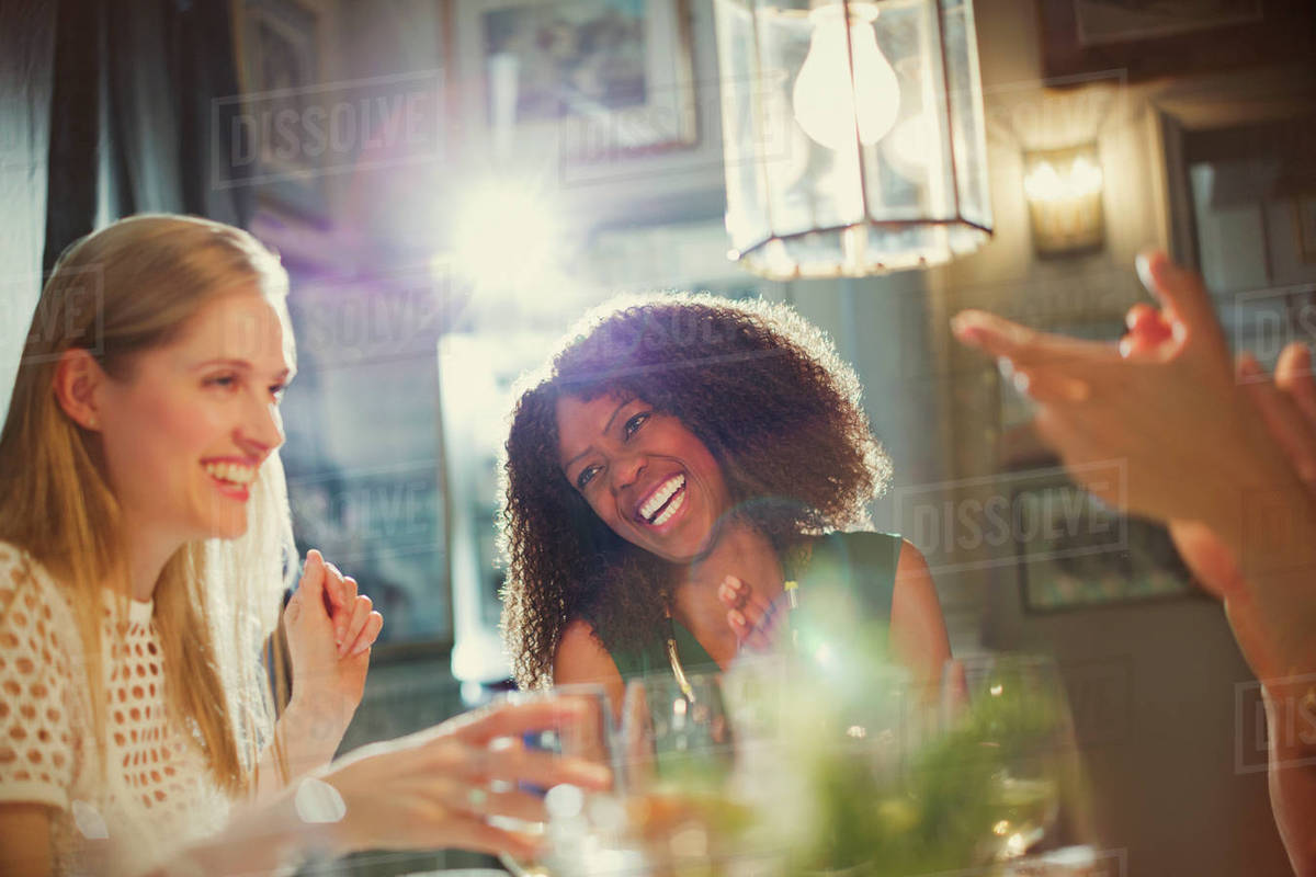 laughing women friends clapping and dining at restaurant table