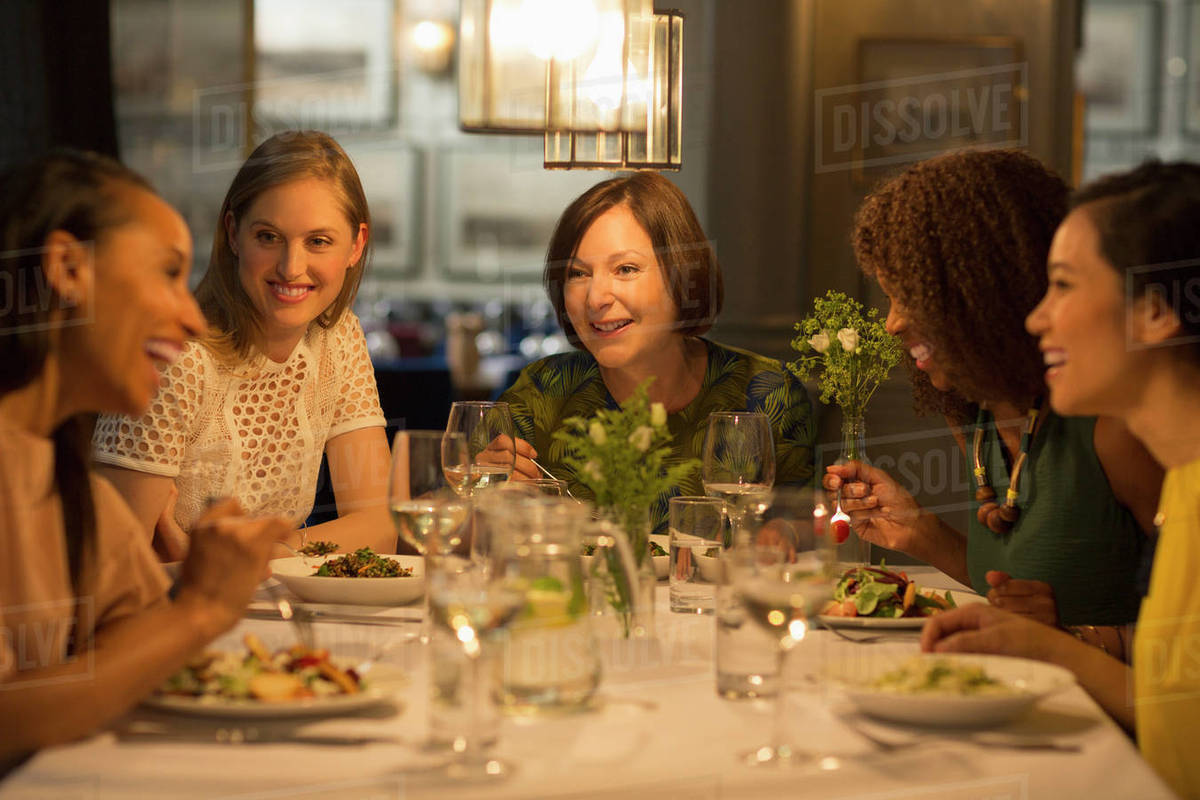 Smiling Women Friends Dining At Restaurant Table Stock Photo Dissolve