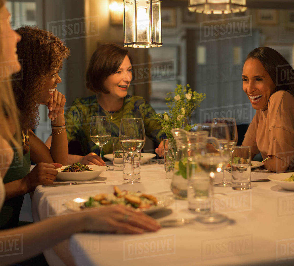 Women Friends Dining And Talking At Restaurant Table Stock Photo Dissolve