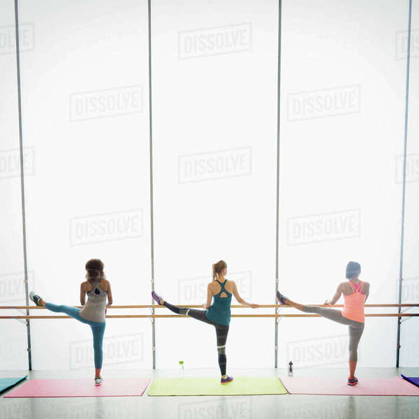 Women stretching legs at barre in exercise class gym studio Royalty-free stock photo