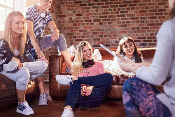 Young adult dancer friends with headphones talking and hanging out in studio Royalty-free stock photo