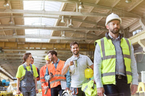 Steel workers talking and walking on coffee break in factory Royalty-free stock photo
