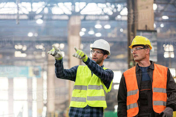 Steel workers talking and pointing in factory Royalty-free stock photo