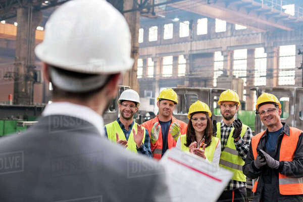 Steel workers clapping for manager in meeting in factory Royalty-free stock photo